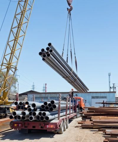 Delivery of steel pipes being unloaded with a crane